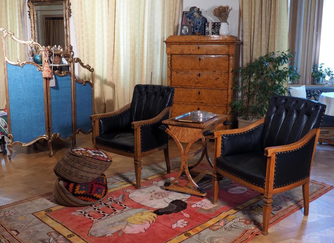 Маленькая заводь ковра и островок мебели перед телевизором.